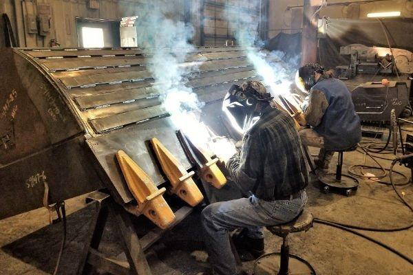two men welding a Felco bucket